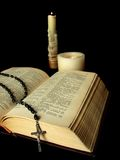 Rosary, old book and candles. Rosary laying on old book by the candlelight Stock Photography