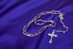 Rosary on Purple Background Stock Photos