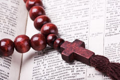 Rosary with a wooden cross lying on open Bible Stock Photos