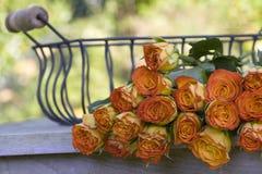 Rosas alaranjadas bonitas em uma cesta do ferro Imagem de Stock