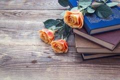 Rosas alaranjadas e uma pilha de livros em placas de madeira velhas Copie termas Imagens de Stock