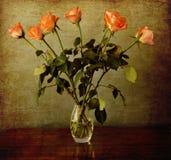 Rosas alaranjadas em um vaso em um fundo do vintage do grunge Imagem de Stock Royalty Free