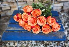 Rosas alaranjadas em uma cadeira rústica azul Foto de Stock Royalty Free