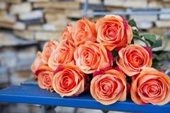 Rosas alaranjadas em uma cadeira rústica azul Imagem de Stock Royalty Free