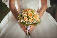 Rosas alaranjadas nas mãos da noiva Fotos de Stock
