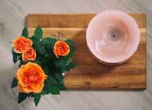 Rosas alaranjadas no fundo da placa de madeira no potenciômetro imagem de stock royalty free