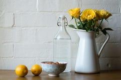 Rosas amarillas con los limones, las almendras y agua Foto de archivo libre de regalías