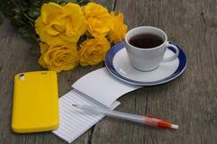 Rosas amarillas, cuaderno, café y teléfono amarillo Foto de archivo libre de regalías