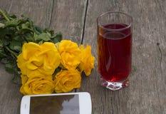 Rosas amarillas, el teléfono móvil y vidrio de jugo en una tabla de madera Foto de archivo libre de regalías
