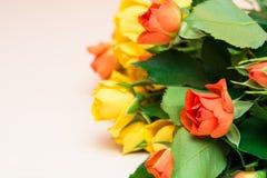 Rosas amarillas y anaranjadas en un fondo de madera ligero foto de archivo