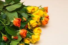 Rosas amarillas y anaranjadas en un fondo de madera ligero fotografía de archivo