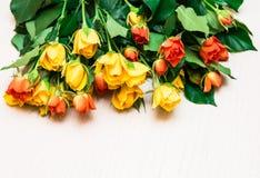 Rosas amarillas y anaranjadas en un fondo de madera ligero Women s d imagen de archivo libre de regalías