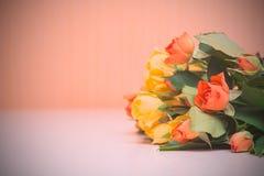 Rosas amarillas y anaranjadas en un fondo de madera ligero Women s d fotografía de archivo