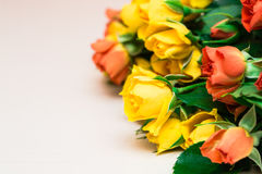 Rosas amarillas y anaranjadas en un fondo de madera ligero Women s d foto de archivo
