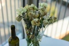 Rosas amarillas y botella de vino marchitadas Imágenes de archivo libres de regalías