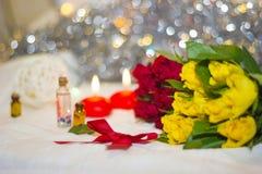 Rosas amarillas y rojas con el primer de las velas Imagen de archivo libre de regalías