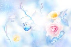Rosas amarillas y rosadas hermosas y mariposa azul en la imagen natural del invierno colorido artístico de la nieve y de la helad foto de archivo libre de regalías