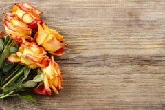 Rosas anaranjadas en fondo de madera Imagen de archivo libre de regalías