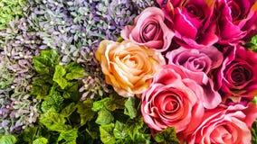 Rosas artificiais e flores do fundo decorativo em uma parede Imagem de Stock