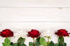 Rosas artificiais no fundo de madeira Fotografia de Stock