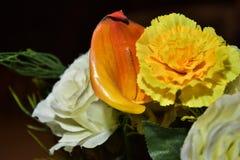 Rosas artificiales blancas y lirios amarillos en una noche plástica del florero Fotografía de archivo libre de regalías