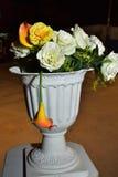 Rosas artificiales blancas y lirios amarillos en una noche plástica del florero Fotos de archivo libres de regalías