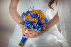 Rosas azuis nas mãos da noiva Foco em flores Imagem de Stock Royalty Free