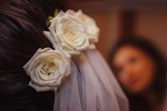 Rosas blancas en el pelo del ` s de la novia, estilo para una boda Fotos de archivo libres de regalías
