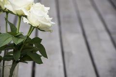 Rosas blancas en florero en el pórtico de madera Fotos de archivo libres de regalías