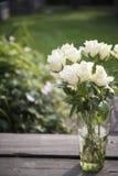 Rosas blancas en florero en el pórtico de madera Imágenes de archivo libres de regalías