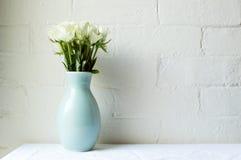 Rosas blancas en florero verde en el mantel blanco contra el ladrillo blanco Imagen de archivo libre de regalías