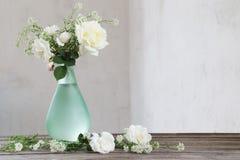 Rosas blancas en florero verde en la tabla de madera Imagenes de archivo