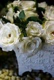 Rosas blancas en plantador adornado foto de archivo