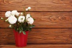 Rosas blancas en un cubo rojo Foto de archivo