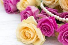 Rosas bonitas em um fundo de madeira branco Imagem de Stock