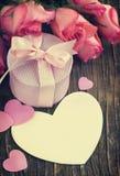 Rosas, caja de regalo y tarjeta de felicitación rosadas con el espacio de la copia Imagen de archivo libre de regalías
