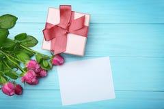 Rosas, caja de regalo y tarjeta vacía en fondo de madera imagen de archivo libre de regalías