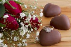 Rosas, chocolates del corazón y anillo Imagen de archivo