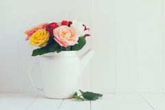 Rosas coloridas no potenciômetro branco do café do esmalte fotos de stock royalty free