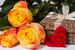 Rosas con un regalo y un corazón foto de archivo