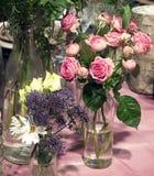 Rosas cor-de-rosa bonitas e flores selvagens no vidro na toalha de mesa Fotos de Stock Royalty Free