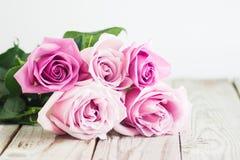 Rosas cor-de-rosa borradas no fundo de madeira Foto de Stock