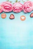 Rosas cor-de-rosa com chocolate do coração e mensagem romântica do amor no fundo azul, vista superior Fotografia de Stock Royalty Free