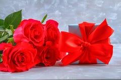 Rosas cor-de-rosa com uma caixa de presente amarrada com uma curva Molde para o 8 de março, o dia de mãe, o dia de Valentim Fotografia de Stock