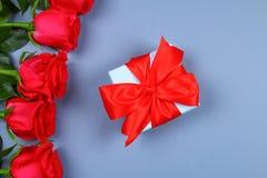 Rosas cor-de-rosa com uma caixa de presente amarrada com uma curva Molde para o 8 de março, o dia de mãe, o dia de Valentim Fotos de Stock Royalty Free