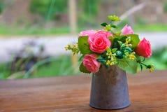 Rosas cor-de-rosa no vaso do metal na tabela de madeira pela janela Fotos de Stock Royalty Free