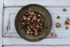 Rosas cor-de-rosa secadas pequenas na placa de bronze do vintage fotografia de stock