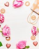 Rosas, coração do chocolate e saco de compras com os cartões da mensagem do amor no fundo de madeira branco Imagens de Stock
