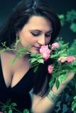 Rosas de cheiro da menina fotografia de stock