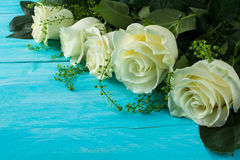 Rosas de marfil en fondo de madera de la turquesa foto de archivo